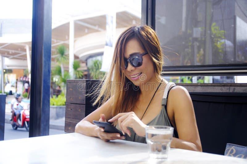 Schöne und glückliche Asiatin, die den Handy an herein simst verwendet stockfotografie