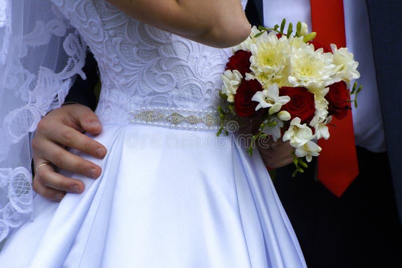 Schöne und glückliche junge Braut und Bräutigam im Hochzeitskleid lizenzfreies stockbild