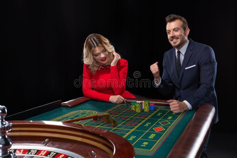 Schöne und gut gekleidete Paare, die Roulette im Kasino spielen lizenzfreie stockbilder