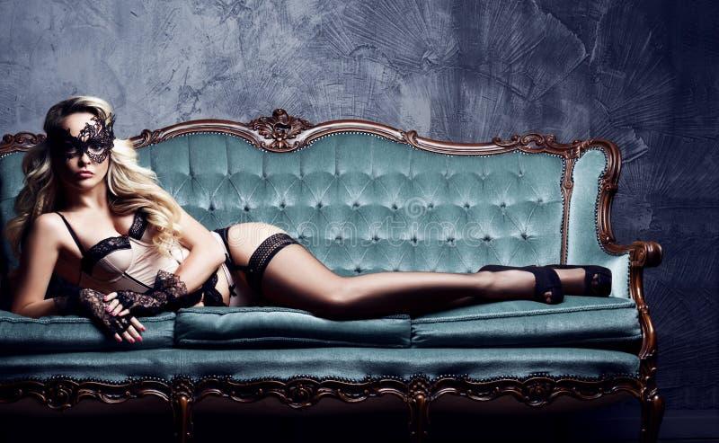 Schöne und junge Frau, die in der sexy Wäsche und in venetianischem m aufwirft lizenzfreies stockbild