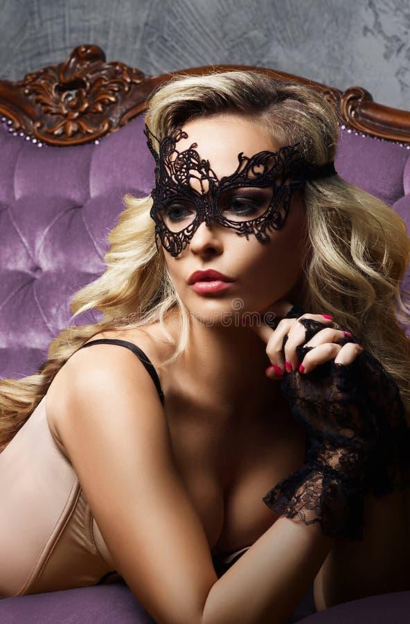 Schöne und junge Frau, die in der sexy Wäsche und in venetianischem m aufwirft lizenzfreies stockfoto