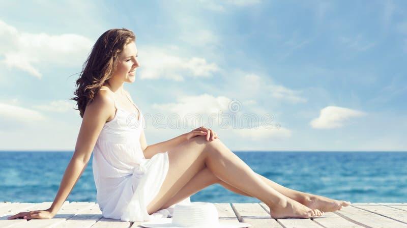 Schöne und junge Frau, die im weißen Kleid auf einem hölzernen Pier aufwirft lizenzfreie stockbilder