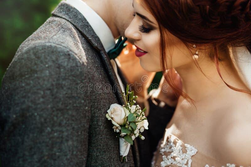 Schöne und junge Paare, die zusammen nahe dem grünen Busch stehen lizenzfreie stockfotografie