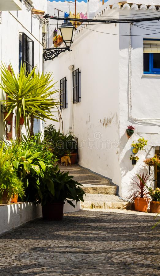 Schöne und malerische schmale Straße mit weißen Fassaden von BU lizenzfreie stockfotos
