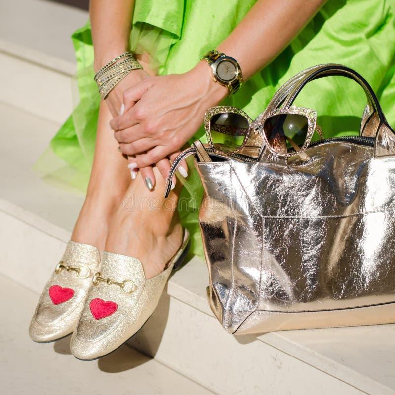 Schöne und moderne Schuhe auf Frauen ` s Bein Frau Stilvolles Damenzubehör Goldschuhe, Tasche, lindgrünes Kleid oder Rock stockfotografie
