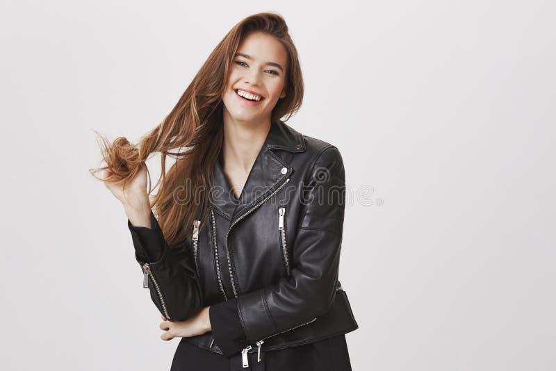 Schöne und Rebellenfrau, die mit dem Haar spielt Porträt des reizend modernen europäischen Mädchens beim Lederjackeberühren lizenzfreie stockbilder