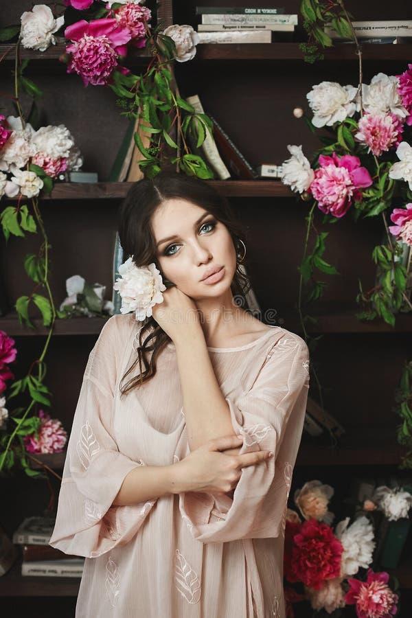 Schöne und sexy junge Brunettemodellfrau, im grauen Kleid, wirft mit Blumen in der Bibliothek auf stockbild