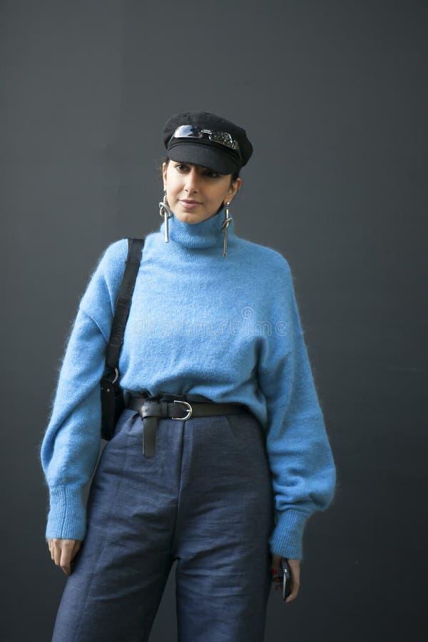 Schöne und stilvolle a-Frau in einer Kappe, in einer blauen Mohärstrickjacke, in Blue Jeans und in den langen Ohrringen kleiden d lizenzfreies stockfoto