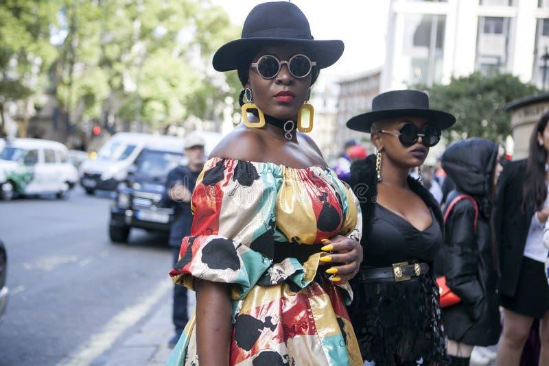 Schöne und stilvolle Frau im colrful gelben hübschen Kleid, das während der London-Mode-Woche aufwirft externer Eudon Choi stockbild