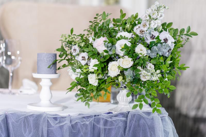 Schöne und vorzügliche Dekoration der Hochzeitsfeier Bewirten Sie gediente Tabelle mit einer blauen Tischdecke, Platten festlich  stockbild