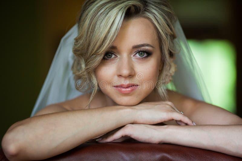 Schöne unschuldige blonde Braut, die an der Stuhlnahaufnahme sich lehnt lizenzfreie stockfotografie
