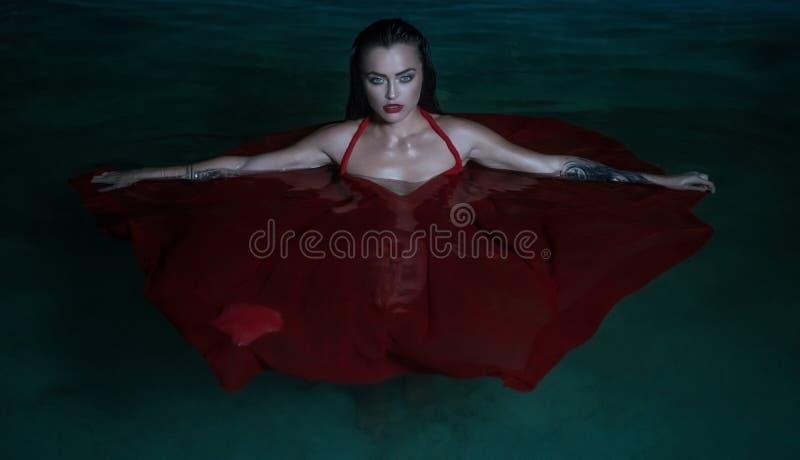 Schöne verlockende Frau, die rotes Kleid Pool im im Freien nachts trägt lizenzfreie stockfotos