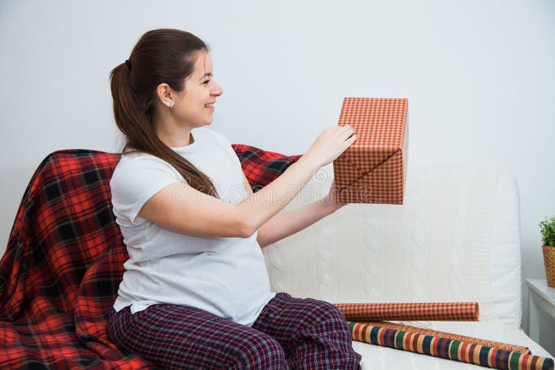 Schöne Verpackung der schwangeren Frau stellt sich für Weihnachten, Geschenkverpackung dar stockfotografie