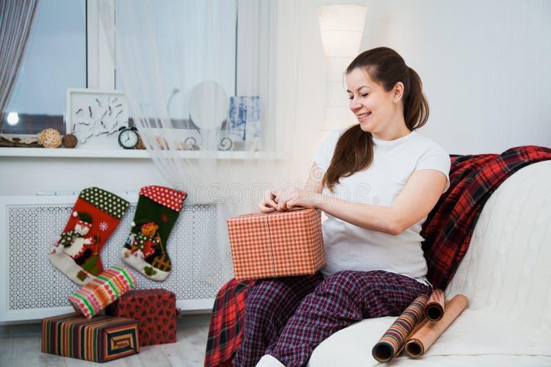 Schöne Verpackung der schwangeren Frau stellt sich für Weihnachten, Geschenkverpackung dar lizenzfreie stockbilder