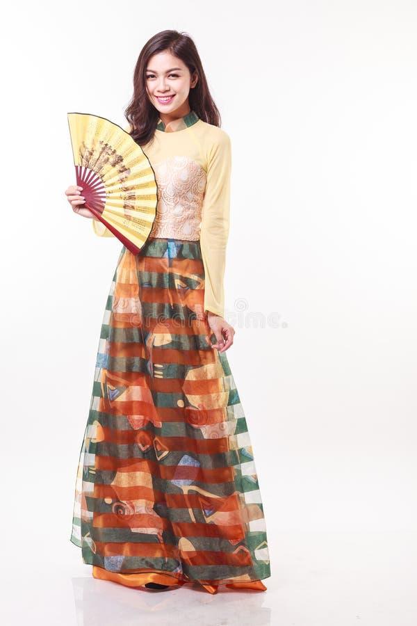 Schöne vietnamesische junge Frau mit moderner Art AO Dai, das einen Papierfan auf weißem Hintergrund hält stockbild
