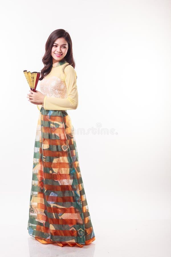 Schöne vietnamesische junge Frau mit moderner Art AO Dai, das einen Papierfan hält stockfotos