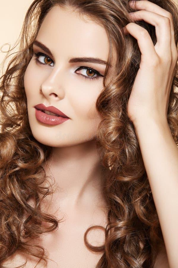 Schöne vorbildliche berühren ihr langes glänzendes lockiges Haar lizenzfreies stockfoto