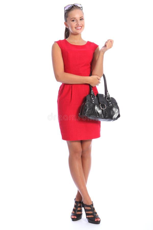 Schöne vornehme junge Frau in den roten Kleid-hohen Absätzen lizenzfreie stockfotografie
