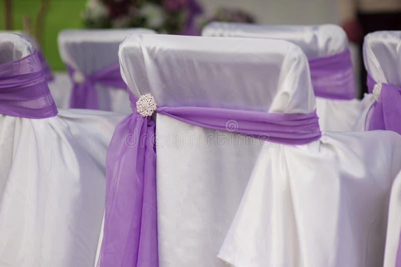 Schöne weiße Hochzeitsstühle verziert mit purpurroten Bögen stockfotografie