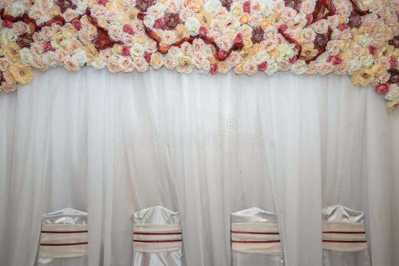 Schöne weiße Hochzeitsstühle verziert mit purpurroten Bögen lizenzfreie stockfotografie