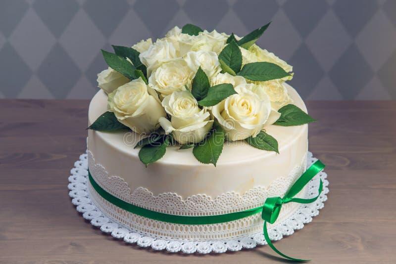 Schöne weiße Hochzeitstorte verziert mit Blumenstrauß von weißen Rosen der Blumen Konzept von eleganten Feiertagsnachtischen lizenzfreie stockbilder