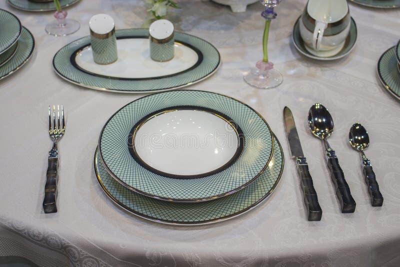 Schöne weiße Platten des Türkisblaus mit Gold auf der Tischdecke Festliches Gedeck tief und Flacheisenmessergabellöffel stockfoto