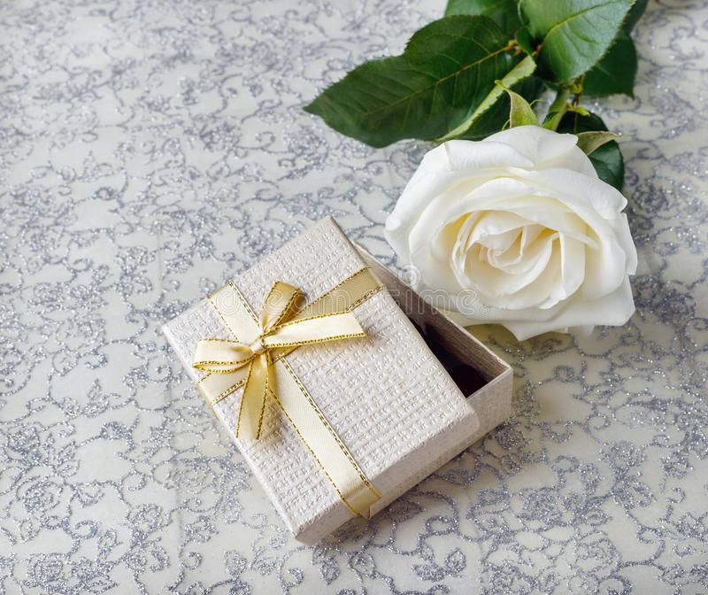 Schöne weiße Rose mit einer goldenen Geschenkbox für Valentinstag lizenzfreie stockfotos