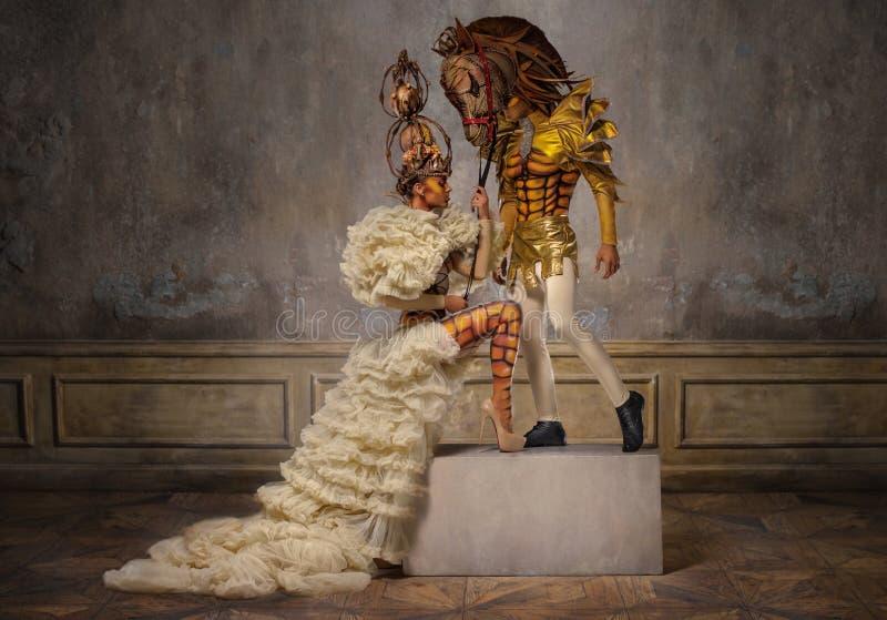 Schöne weiße Schachkönigin mit Mann in der Pferdemaske stockfotos