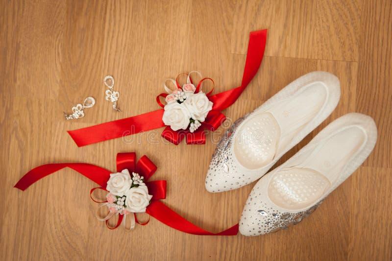 Schöne weiße Schuhe von der Braut mit anderen Stützen stockfoto