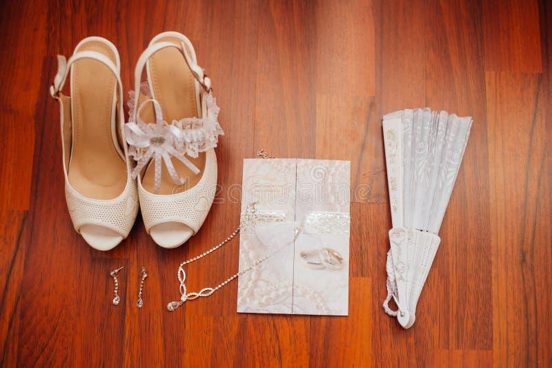 Schöne weiße Schuhe von der Braut mit anderen Stützen stockbilder