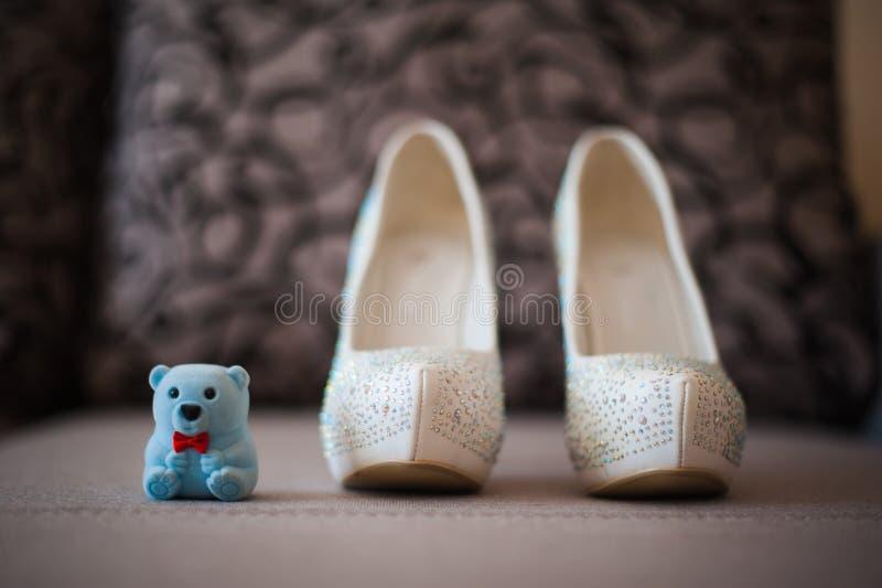 Schöne weiße Schuhe von der Braut mit dem teddybear stockfotos