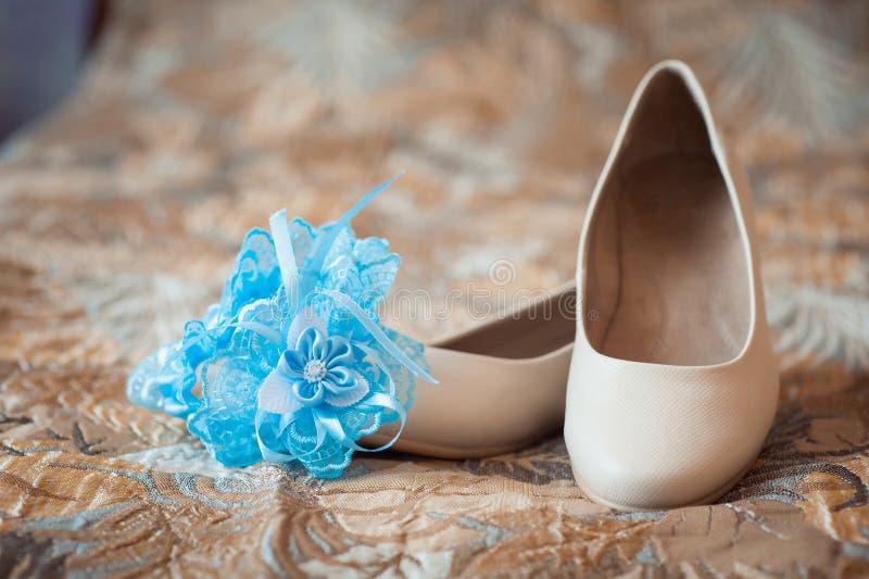 Schöne weiße Schuhe von der Braut mit Strumpfband lizenzfreie stockbilder