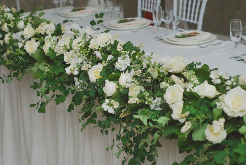 Schöne weiße und grüne Blumen-Dekorations-Anordnung auf Hochzeitstafel Heiratende Brautblumen-Dekoration lizenzfreie stockfotos