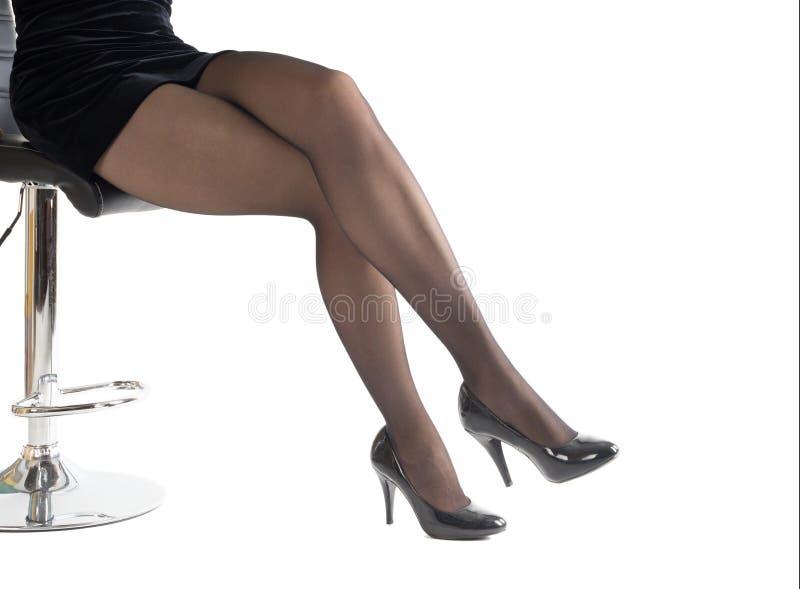 Schöne weibliche Beine in den klassischen schwarzen Schuhen und schwarzen in den Strumpfhosen, lokalisiert auf weißer, Seitenansi lizenzfreies stockbild