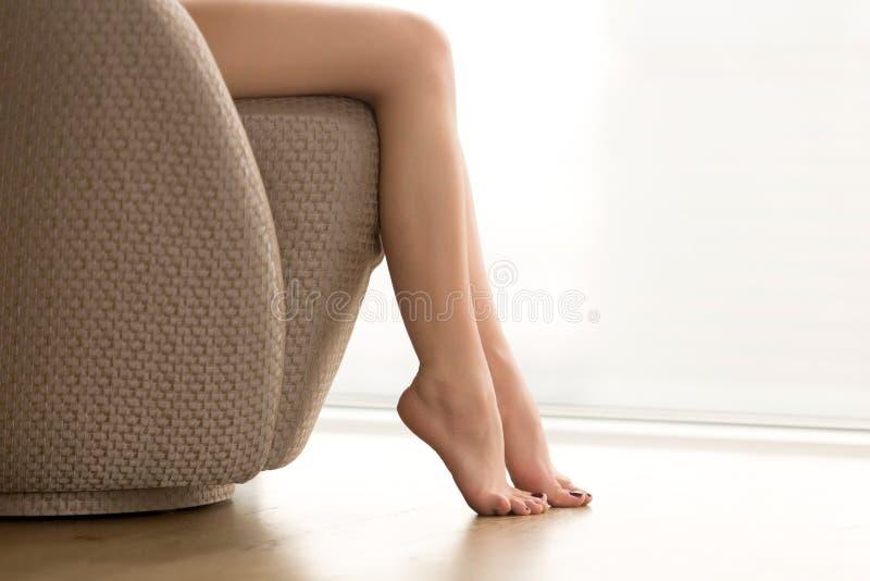 Schöne weibliche Beine, junge Frau, die barfuß auf Lehnsessel sitzt, stockbilder