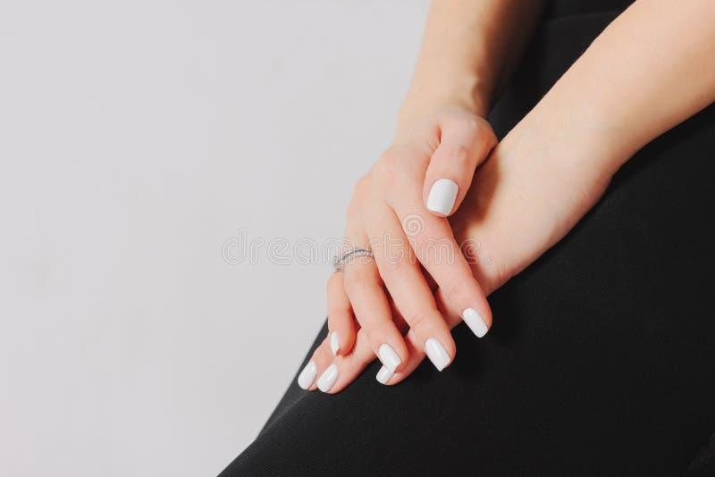 Schöne weibliche Hände mit weißer Maniküre und Verlobungsring O lizenzfreies stockbild