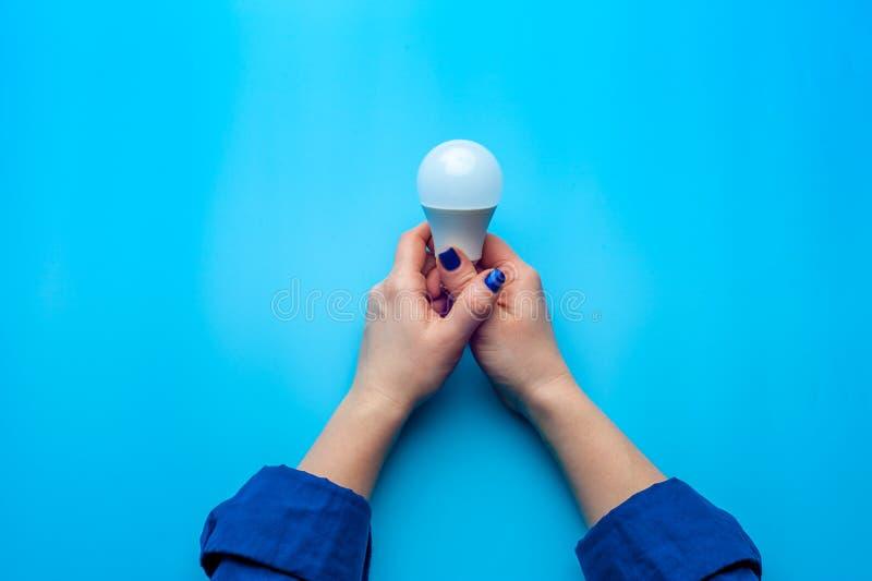 Schöne weibliche Hand der Nahaufnahme, die Glühlampe hält lizenzfreie stockfotos