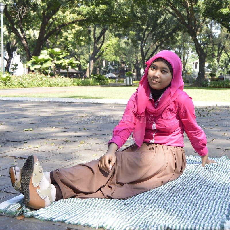 Schöne weibliche Moslems, die draußen 2 sitzen stockbild