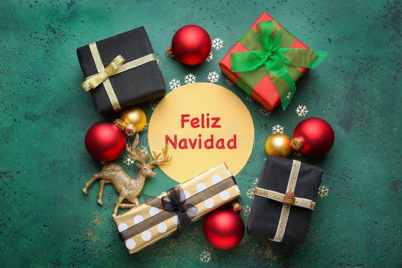 Schöne Weihnachtsdekorationen mit Grußkarte auf Farbhintergrund stockfoto
