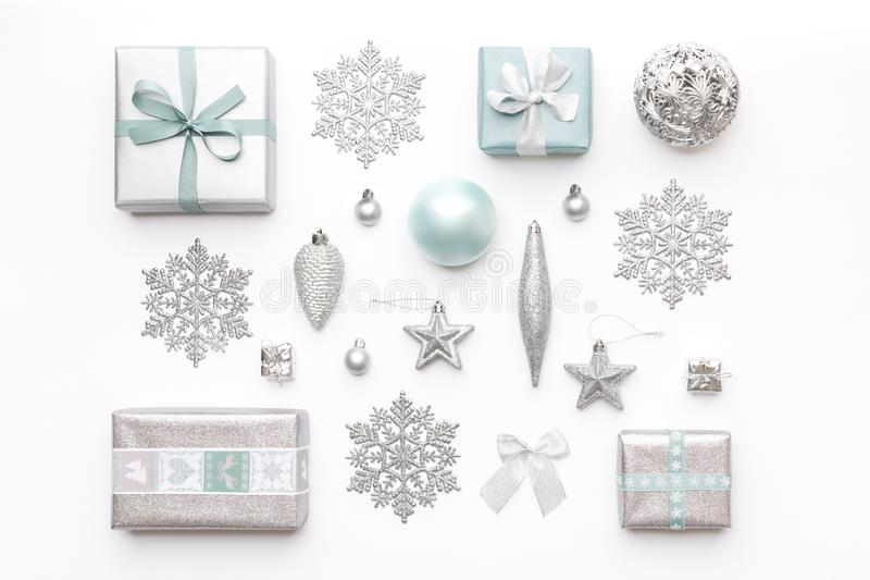Schöne Weihnachtsgeschenke und silberne Schneeflocken und Verzierungen lokalisiert auf weißem Hintergrund Flitter in einem blauen stockfotos