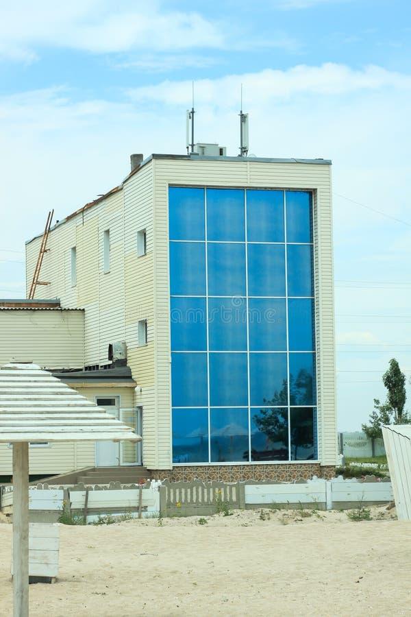Schöne Wohnungen mit Glasfenstern, modernes Architekturhaus durch das Meer, sandiger Strand, blauer bewölkter Himmel stockfotografie