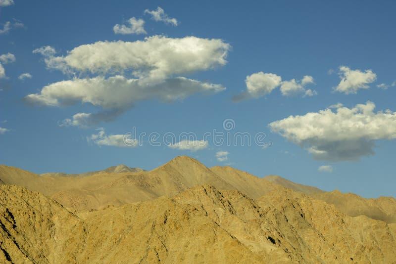 Schöne Wolken über den Bergen im blauen Himmel lizenzfreies stockbild