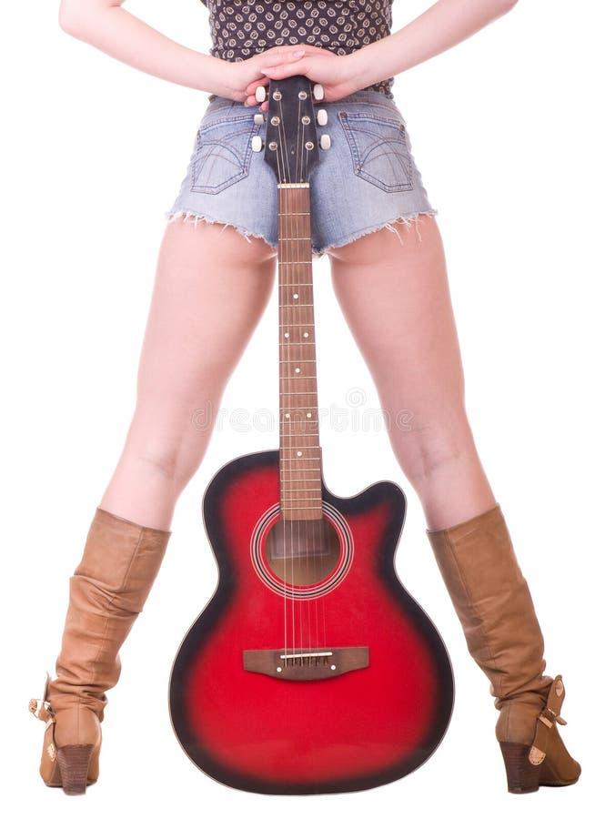 Schöne womanish Fahrwerkbeine mit Gitarre stockfoto