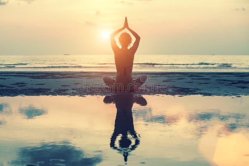 schöne Yogafrau bei Sonnenuntergang in den surrealen Farben lizenzfreie stockbilder