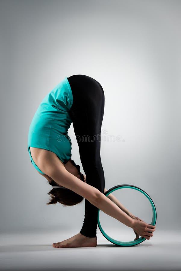 Schöne Yogafrau, die im grauen Hintergrund steht stockfoto