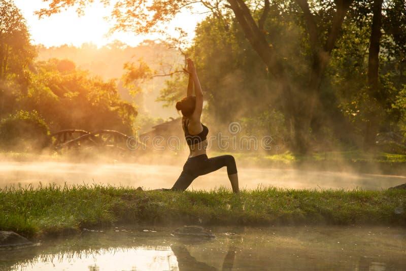 Schöne Yogafrau morgens am Park der heißen Quelle lizenzfreie stockfotografie