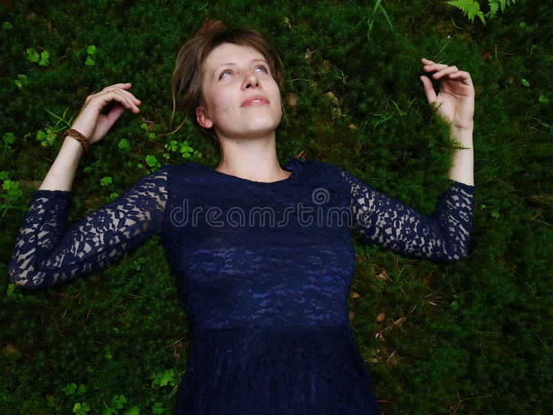Schöne youg Frau, die auf Moos träumt stockfoto