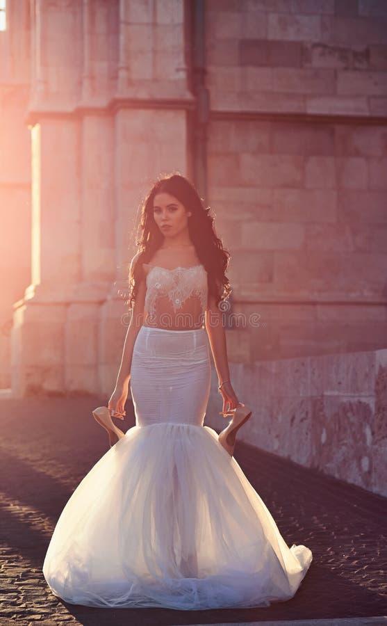 Schöne zarte sexy brunette Braut der jungen Frau Luxusschuhen eines in den weißen Heiratskleidergriffs am Schloss-Sommer stockbilder