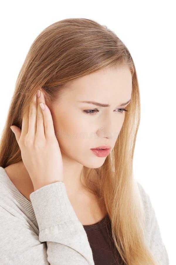 Schöne zufällige Frau berührt ihr Ohr. lizenzfreies stockfoto
