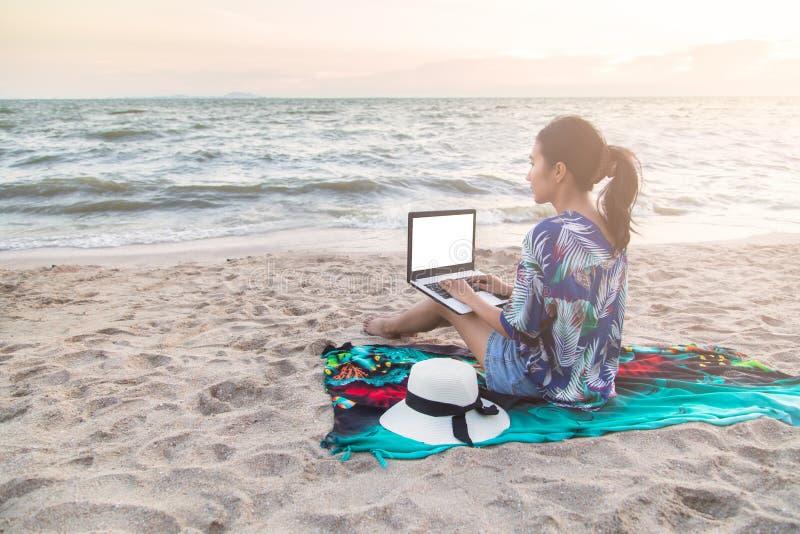 Schöne zufällige Frau mit einem Laptop auf dem Strand lizenzfreies stockfoto